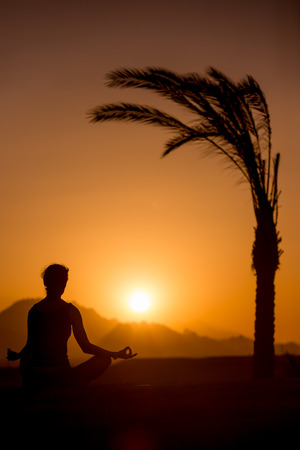sukhasana: Silhouette of young woman practicing yoga in beautiful tropical location with mountains, sitting beside palm tree in sukhasana easy pose, meditating at sunset or sunrise Stock Photo