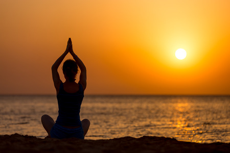 breathe easy: Back view of young woman practicing yoga on the beach, sitting on the seashore at sunset or sunrise in asana Sukhasana, hands above head, copy space Stock Photo
