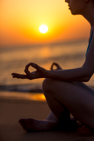 breathe easy: Profile of serene young woman sitting cross-legged, relaxing on the beach, meditating with fingers in yogic Jnana mudra at sunset or sunrise, close up Stock Photo