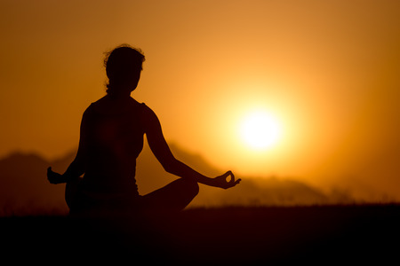yogic: Silhouette of young woman sitting in picturesque serene place with crossed legs in yogic posture, looking at sunset or sunrise in mountains