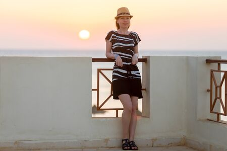 Full length portrait of young smiling woman in straw hat and cute summer dress standing at the balcony with picturesque sea sunset or sunrise view photo