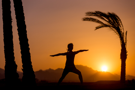 virabhadrasana: Silhouette of young woman practicing yoga or pilates at sunset or sunrise in beautiful tropical location with mountains and palm trees, doing lunge exercise, Warrior II pose, Virabhadrasana 2
