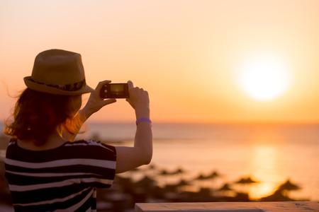 landschap: Jonge vrouw in strohoed en schattig zomerjurkje staan op het balkon met een schilderachtig zee landschap, nemen foto van zonsondergang of zonsopgang op smartphone, achteraanzicht