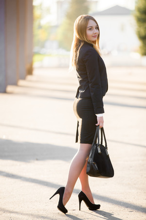 Portrait of young stylish woman on sunny street wearing elegant formal outfit, high heels and black suit with sexy skirt
