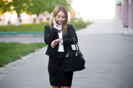 Young fashionable business woman in hurry on city street, looking at her watch in rush, checking time while talking on mobile phone Stock Photo
