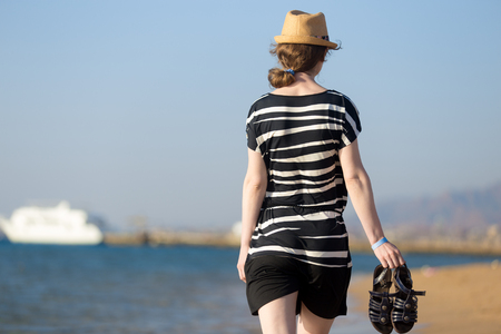 leather hat: Young woman in short dress fluttering in sea breeze walking at sea coast holding her blue leather sandals, back view
