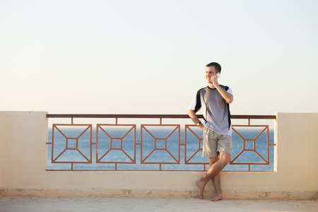 phonecall: Minimalistic portrait of young happy smiling man holding cellphone, making call, talking on phone, standing barefoot in relaxed pose on summer terrace with sea scenery, copy space