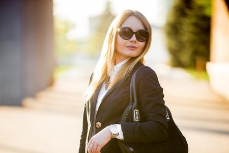 Portret van jonge mooie blonde vrouw met een zonnebril en modieuze zwart pak op een zonnige straat Stockfoto