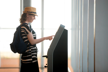 Young woman at self service transfer area doing self-check-in or buying plane tickets at automated machine with touchscreen interactive display in modern airport terminal building
