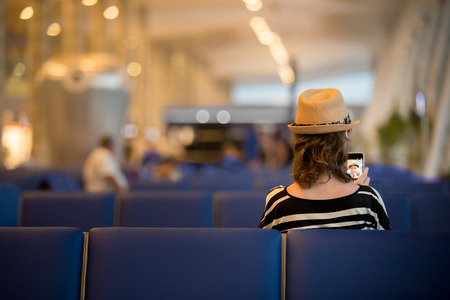 lounge: Young traveling woman waiting for transYoung female traveler in summer dress and straw hat waiting for trip, sitting with smartphone in modern station lounge area with blue seats, back viewport