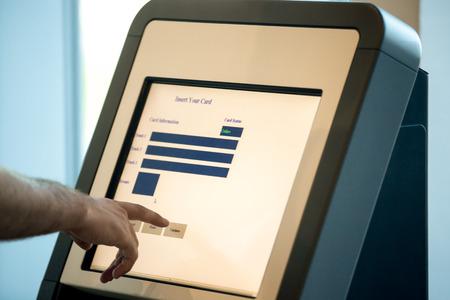 gente aeropuerto: Primer plano de manos de los hombres de visualizaci�n interactiva de tocar en la m�quina de transferencia de auto-servicio, haciendo auto-check-in para el vuelo o la compra de billetes de avi�n en el dispositivo autom�tico en el moderno edificio de la terminal del aeropuerto Foto de archivo