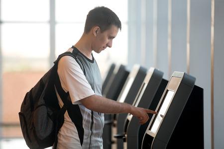 to fly: Hombre joven con mochila pantalla interactiva conmovedora en la m�quina de transferencia de auto-servicio, haciendo auto-check-in para el vuelo o la compra de billetes de avi�n en el dispositivo autom�tico en el moderno edificio de la terminal del aeropuerto