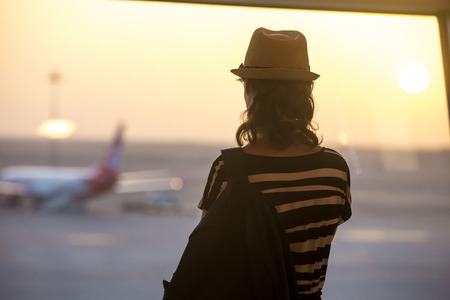 Young woman in straw hat and summer dress with backpack waiting for flight in modern airport terminal building, watching airplanes in window on sunrise or sunset, back view
