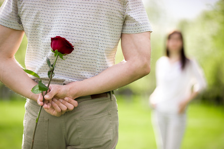 Couple of lovers on a date, focus on young man back who is holding red rose while watching his girlfriend approaching