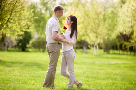 to confess love: Full length portrait of young man and woman on date, meeting in park, standing in front of each other, young man giving red rose to his beautiful happy smiling girlfriend Stock Photo