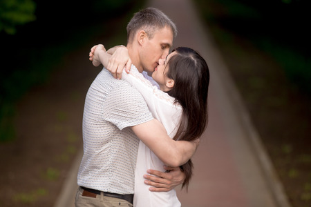 sexual intimacy: Young man kissing his beautiful girlfriend, attractive couple of lovers standing in park in summer on a date, embracing outdoors
