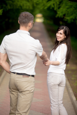 come in: Young brunette woman in white jersey and jeans leading her lover by hand in park, looking at him, playfully laughing, inviting to come with her, follow me concept