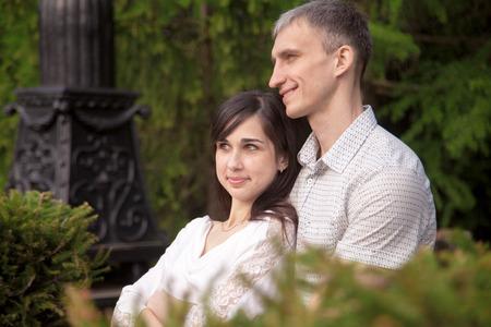 amigos abrazandose: Pareja de enamorados sentados cerca en el banco en el parque en una fecha, relajante al aire libre con expresiones soñando, joven abrazando a su hermosa novia morena