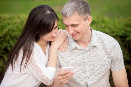 absorbed: Young attractive happy smiling lovers couple in love sitting on park bench, dating, hugging, holding cell phone, looking at screen together, using app, absorbed in phone communication
