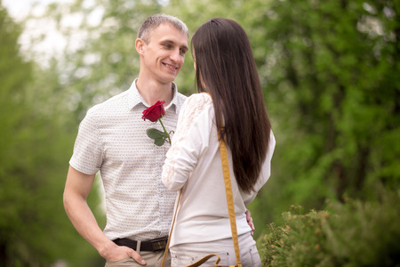 confessing: Couple of lovers meeting on a date in park, looking each other in eyes, smiling young man giving red rose to his brunet girlfriend Stock Photo