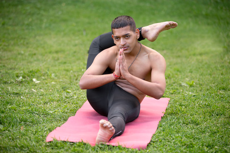 topless: Sporty handsome Indian young man working out on mat on grass in park, doing stretching exercises, Eka Pada Sirshasana, Foot behind the Head Pose, full length, hands in Namaste Banque d'images