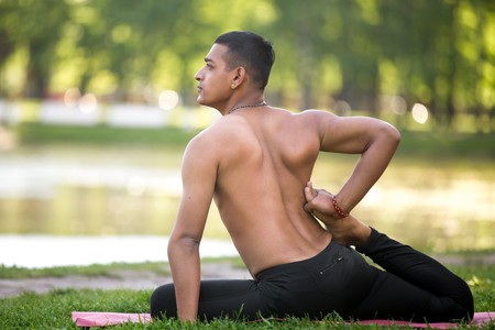 topless: Profile of Handsome sporty Indian young man exercising on lake in park, doing stretching exercises, sitting in Eka Pada Rajakapotasana, full length