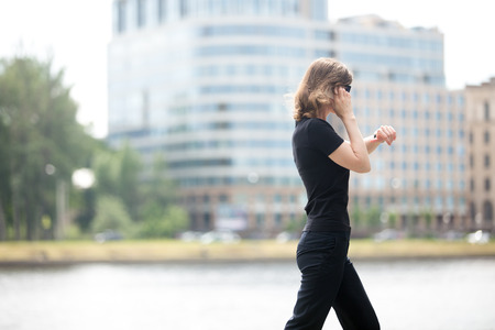 wristwatch: Young confident business woman walking in hurry, looking at watch, talking on mobile phone on the city street in front of blue glass modern office building beside riverbank, profile view