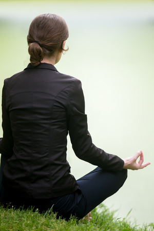 sukhasana: Young woman sitting cross legged on green lake, meditating, practicing yoga Easy Pose, Sukhasana, asana for meditation, pranayama, breathing, back view, vertical shot