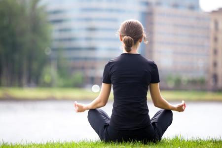 sukhasana: Young woman sitting cross legged on river bank in front of blue glass modern office building, meditating, practicing yoga Easy Pose, Sukhasana, asana for meditation, pranayama, breathing, back view