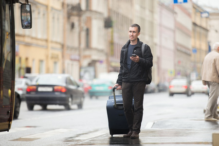 Young smiling handsome man in 20s with luggage bag standing on rainy city street with busy traffic transport using smartphone, waiting for public bus, travelling, wearing casual style clothes Stock Photo