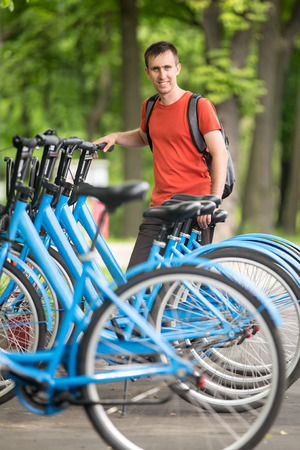 Young happy smiling man standing at rentable city bikes parking lot, choosing bicycle for ride