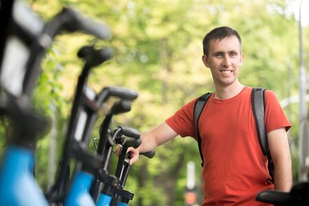 Portrait of young happy smiling man standing at rental city bikes parking lot, renting bicycle for ride