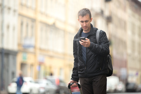 Young smiling attractive man with luggage bag walking in the rainy city street looking at smartphone, using app, gps, searching for direction, texting, making call, travelling, wearing casual clothes