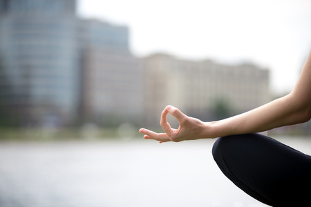 stress: Close up of hands of young office yogi woman sitting cross legged in yoga Easy Sukhasana Pose on riverbank in the city, meditating with fingers in Jnana mudra