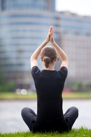 sukhasana: Young business woman sitting cross legged on street in front of blue glass modern office building, practicing yoga Easy Pose, Sukhasana, meditation, pranayama, breathing, full length, back view