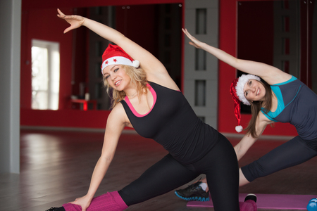 Two pretty girls in santa claus hats do stretching, body bending exercises on mats in sports hall