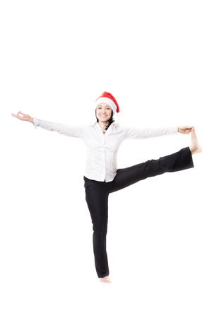 big toe: Smiling young office female in formalwear wearing white shirt and red Santa Claus Christmas hat, standing in yoga position in Utthita hasta padangushthasana (stretched hand grasps big toe), isolated