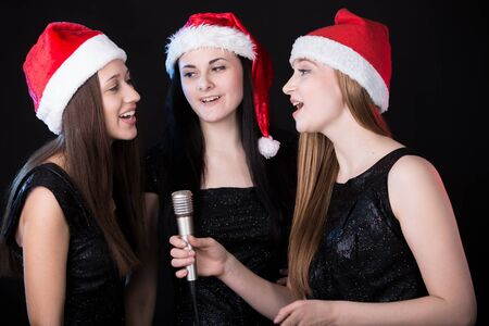 singing: Group of three positive, happy smiling beautiful young female singers singing in cute red santa claus hats, black background