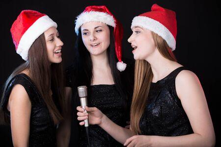 cantaba: Grupo de tres hermosas mujeres cantantes jóvenes positivos, felices sonrientes lindos cantando en rojo santa claus sombreros, fondo negro Foto de archivo