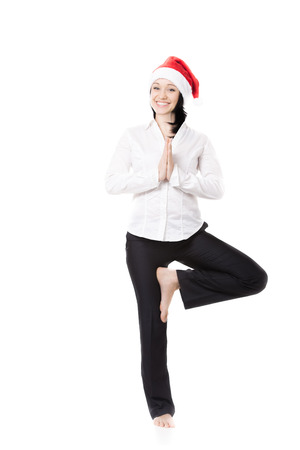 vriksasana: Smiling young office female in formalwear wearing white shirt and red Santa Claus Christmas hat, standing in yoga position vrikshasana (Vriksasana, Tree Pose), isolated Stock Photo