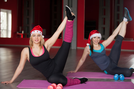 Two pretty girls in santa claus hats do stretching exercises on mats in sports hall Stock Photo