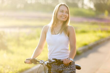 Portrait of beautiful laughing young woman sitting on mountain bike wearing casual white tank top and jeans on park road on bright sunny summer day