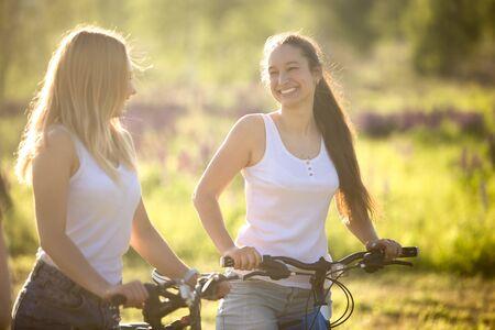 amistad: Dos j�venes hermosas mujeres alegres novias llevaba jeans cortos en bicicleta en el parque el d�a soleado de verano, con una buena vez, feliz riendo juntos