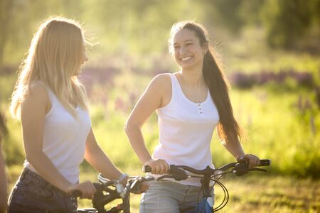 amicizia: Two young beautiful cheerful women girlfriends wearing jeans shorts on bicycles in park on sunny summer day, having good time, happy laughing together