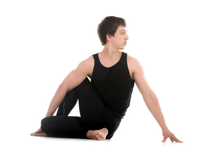 ardha: Sporty attractive young man working out, siting in Half lord of the fishes pose, Ardha Matsyendrasana, therapeutic for digestive organs, spinal cord and back, studio shot, full length