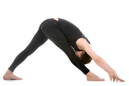 poses de modelos: Perfil del hombre joven deportiva que se resuelve, de pie en actitud de la yoga de la pirámide, la variación de profundidad Parsvottanasana, ejercicio para los hombros, columna vertebral y las piernas flexibilidad, de cuerpo entero Foto de archivo
