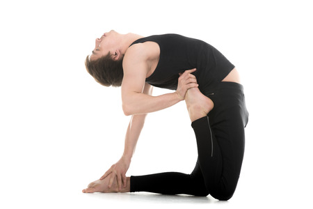ushtrasana: Sporty young man working out, doing yoga, pilates or fitness training, standing on his knees on white background in one legged variation of asana ushtrasana, camel pose, full length Stock Photo
