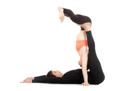 acrobatics: Sporty couple on white background doing acrobatics yoga training, young yogini performing handstand with partner support, studio shot, full length