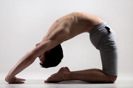 seins nus: Sporty jeune homme musclé en travaillant, de flexion à Little Thunderbolt Pose ou Laghu Vajrasana, fond gris, bas tourné en studio clé, pleine longueur Banque d'images