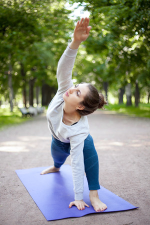 utthita: Serene beautiful sporty young woman working out in park alley, doing warming up stretching exercise, standing in Utthita Parsvakonasana, Extended Side Angle Pose, full length Stock Photo